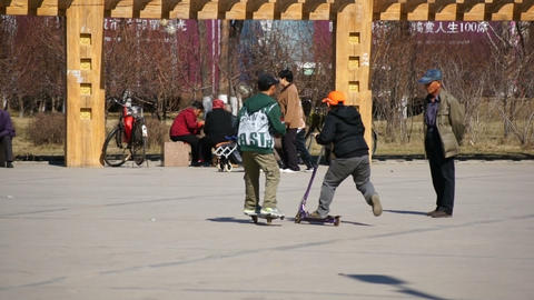 Town Heihe (China). Vacationers people and children playing in the park Live Action