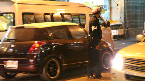 Policeman on night street in Bangkok Footage