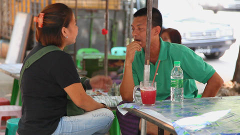 Pair drink cane juice in street cafe Stock Video Footage