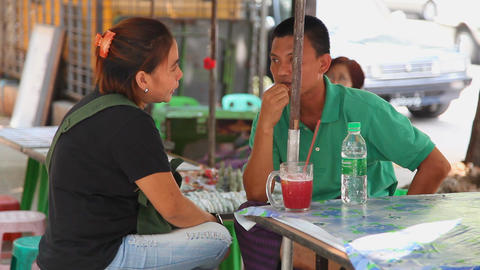 Pair drink cane juice in street cafe Footage
