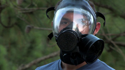 A solider puts on his gas mask in the forest Stock Video Footage