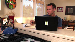 A student takes notes while typing on his laptop Stock Video Footage