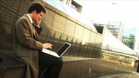 Businessman on laptop and mobile in city Stock Video Footage