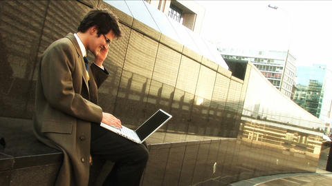 Businessman on laptop and mobile in city Footage