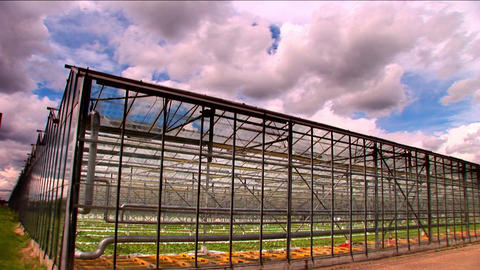 Timelapse clouds roll over a large greenhouse farm Footage