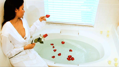 Beautiful latino girl dropping scented petals into bath... Stock Video Footage