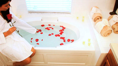 Beautiful latino girl dropping scented petals into bath at a health & beauty spa Footage