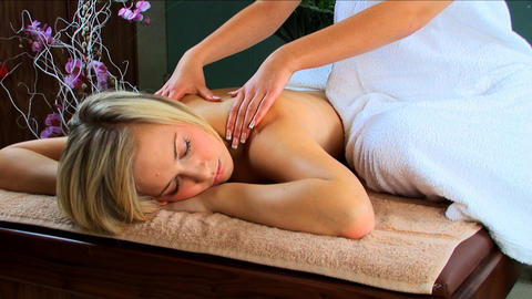 Beautiful blonde girl having massage treatment at a health & beauty spa Footage