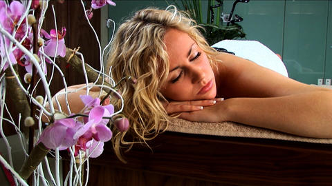 Beautiful blonde girl having hot stones massage treatment at a health & beauty spa Footage