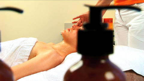 Beautiful blonde girl having facial massage at beauty spa with lotion bottles in foreground Footage