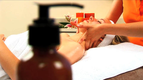 Beautiful blonde girl at health spa having massage treatment with lotion bottles in foreground Footage