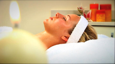 Beautiful blonde girl relaxing at health spa with candles burning Footage