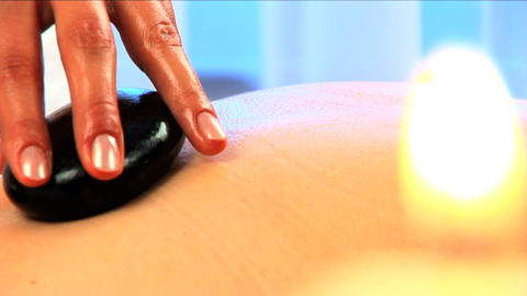 Blonde girl has hot stone massage in close-up with... Stock Video Footage
