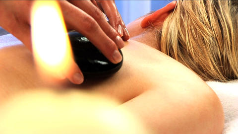 Blonde girl has hot stone massage with candles burning in... Stock Video Footage
