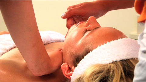 Beautiful blonde girl having facial massage at a health &... Stock Video Footage