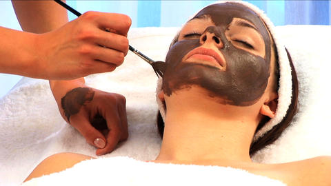 Young brunette girl having facial skin mask applied at health & beauty spa in close-up Footage
