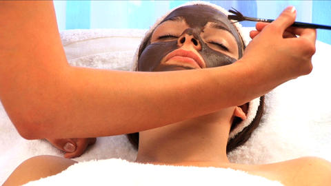 Young brunette girl having facial skin mask applied at... Stock Video Footage