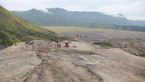 Indonesian people and horses between volcanos Batok and Bromo Footage