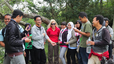 Caucasian woman shooting with Indonesian teenagers Stock Video Footage