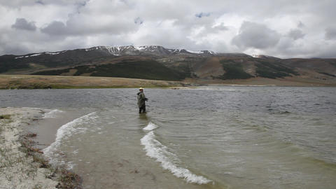 Fisherman With Spinning Catching Fish In Mountain Lake Dayan Nuur stock footage