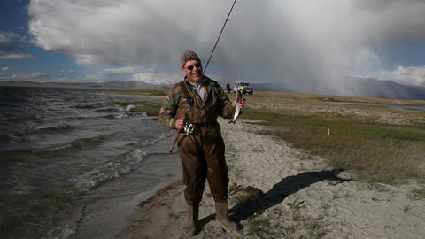 Fisherman with spinning catching fish in mountain lake Dayan Nuur Footage