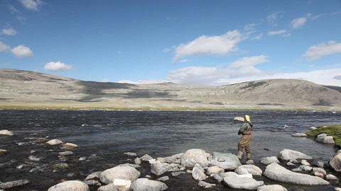 Fisherman with spinning catching fish in mountain river Stock Video Footage