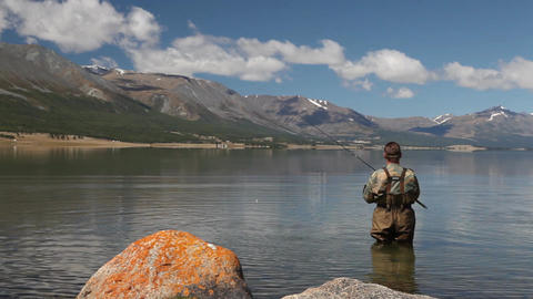 Fisherman with spinning catching fish in Khoton Nuur lake Stock Video Footage