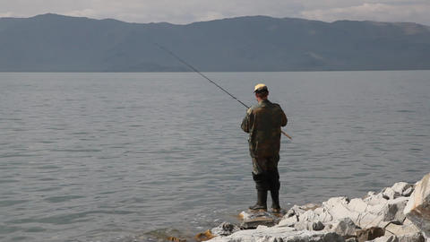 Fisherman with spinning catching fish in mountain lake... Stock Video Footage