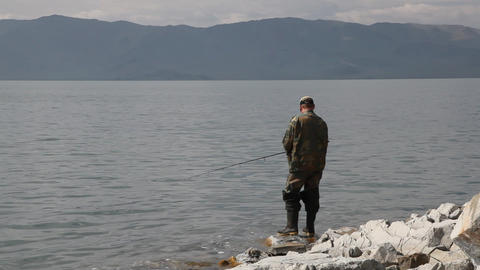 Fisherman with spinning catching fish in mountain lake Tolbo Nuur Footage