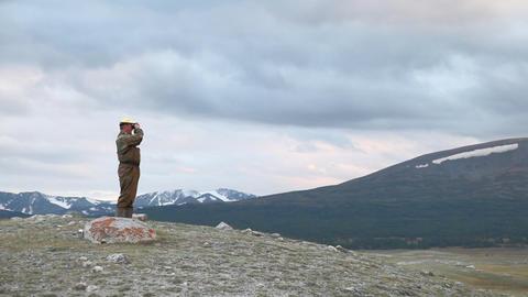 Hiker in mountain look into binoculars Footage
