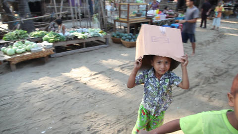 Children play at fishing village market Stock Video Footage