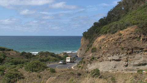 Litte white bus driving down at the Great Ocean Ro Footage