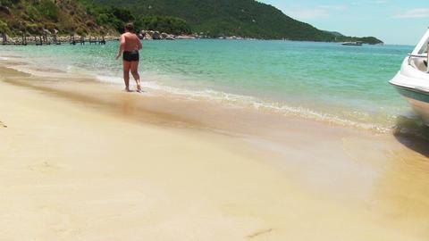 Boy runs into tropical sea Footage