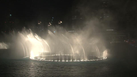 The Dubai Fountain tilt to the burj khalifa Stock Video Footage