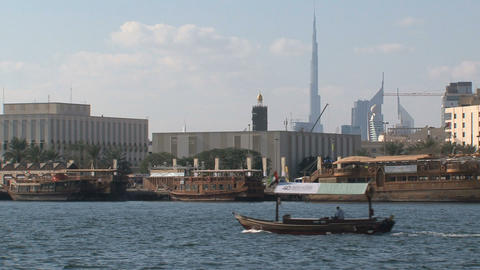Little ferry passing by with the Burj khalifa at the background Footage