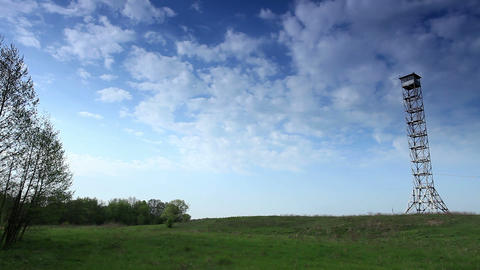 movement of clouds over a field and an observation tower... Stock Video Footage