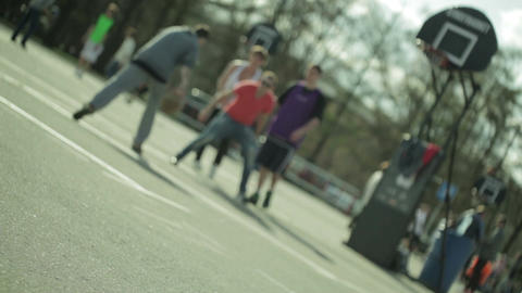 Teenagers playing basketball in a city park. Blured Stock Video Footage