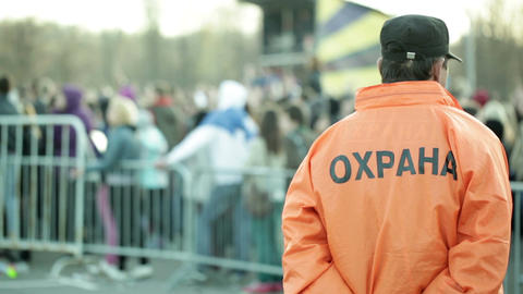 Back of a security guard in front of blurred crowd Stock Video Footage