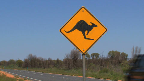 Red jeep passing by Kangaroo sign Stock Video Footage