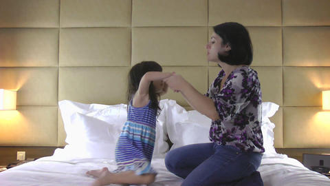 mother and daughter jumping on bed Stock Video Footage