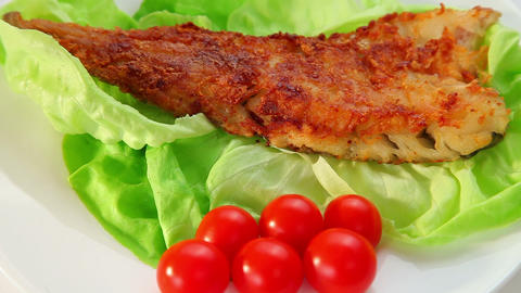 Fried fish dish - fish fillet, green salad and tomatoes Footage
