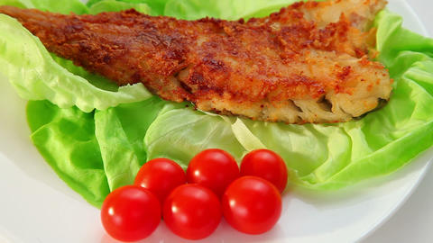 Fried fish dish - fish fillet, green salad and tomatoes Stock Video Footage