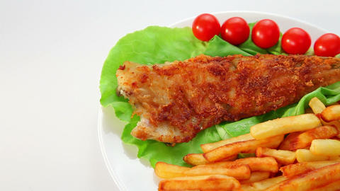 Fried fish dish - fish fillet on green salad with chips... Stock Video Footage