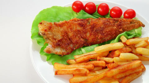 Fried fish dish - fish fillet on green salad with chips and tomatoes Footage