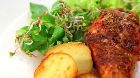 Roasted chicken leg with potatos sprouts salad and tomatoes Stock Video Footage