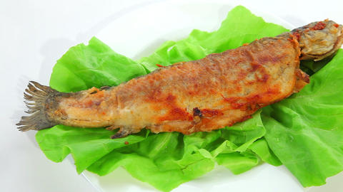 Fried fish on green salad Stock Video Footage