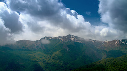Time lapse of cloudy sky over mountain peaks, 4K, UHD Stock Video Footage