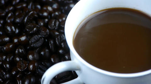 pouring milk into a cup of coffee & coffee beans... Stock Video Footage
