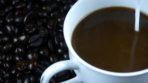 pouring milk into a cup of coffee & coffee beans background,top view Footage