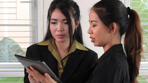 Two Attractive Asian Office Workers Use Tablet Stock Video Footage